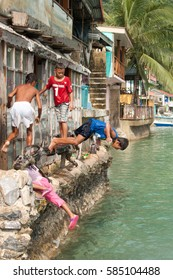 EL NIDO, PHILIPPINES - June 24, 2014: Filipino kids playing in the water, jumping from the house balcony into the water, El Nido, Philippines