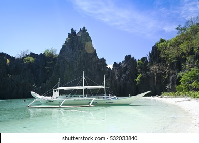 El Nido, Philippines - May 18, 2007: tourists snorkel around banka tour boat in hidden karst lagoon. El Nido is one of the top tourist destinations in the world.