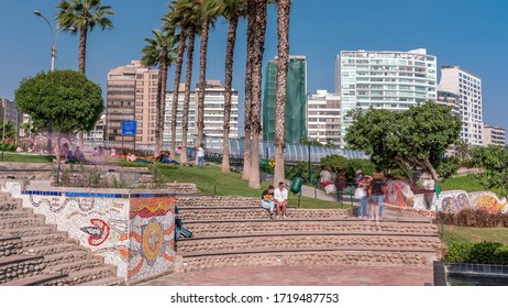 El Parque del Amor or Love park view in Miraflores, Lima, Peru. View from The Kiss statue to bridge Puente Mellizo Villena Rey with people sitting and walking around. Palms and green grass with