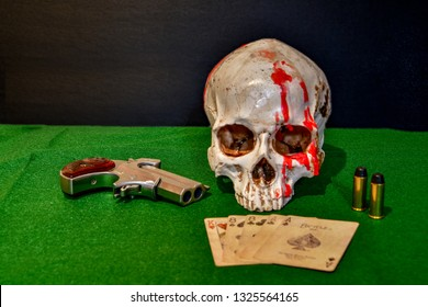 El Paso, Texas - 27 February 2019: A human skull with red candle wax running down one side and a derringer and two bullets. Poker game with the dead man's hand, a pair of aces and eights.