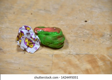 El Paso, Texas, / USA- 14 June 2019 Discarded bubble gum wrapper on wooden floor