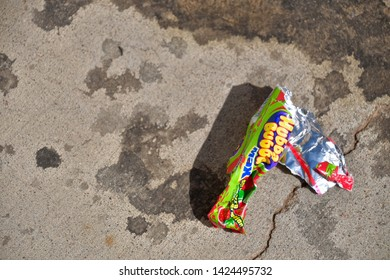 El Paso, Texas, / USA- 14 June 2019 Discarded bubble gum wrapper on concrete walkway.
