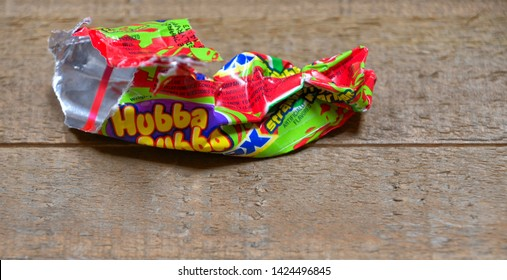 El Paso, Texas, / USA- 14 June 2019 Discarded bubble gum wrapper on wood surface.