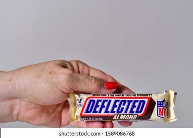 "El Paso, Texas / USA: Circa December 2019 A bar of Snickers brand candy with the football term ""deflected"" being held by a mature Caucasian woman with beautiful  red fingernails."