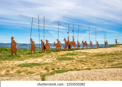EL PERDON MOUNTAIN, SPAIN - MAY 08, 2017: El Perdon Monument to the Pilgrim's Way to Compostela and a male cycling pilgrim who takes a picture of the Pamplona basin with his phone