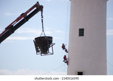 El Pilar de la Mola, España; 06  06 2018: Lighthouse and some workers climbing through it to do masonry and painting work, and a crane with a cement mixer