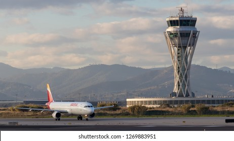 El Prat, Barcelona, España - 12/14/2018 - An Iberia Airbus A321 waits to take off next to the runway with the ATC Tower in the background at sunset