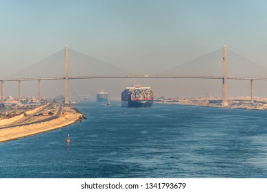 El Qantara, Egypt - November 5, 2017: Container vessel ships passing Suez Canal in the sandy haze in Egypt. The Mubarak Peace Bridge is a road bridge crossing the Suez Canal at El-Qantara.