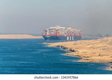 El Qantara, Egypt - November 5, 2017: Large container vessel ship MSC Maya passing Suez Canal in the sandy haze in Egypt.