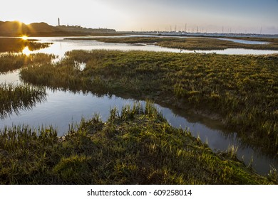 El Rompido lighthouse and marina at sunrise from marshlands, Huelva, Spain