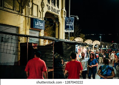 EL SALVADOR - DECEMBER 25: People walking in downtown at night and passing in front of well known bar called La Dalia , December 25, 2019 in San Salvador, El Salvador