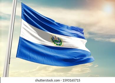 El Salvador national flag cloth fabric waving on the sky with beautiful sun light