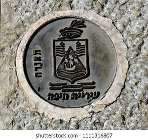 elaborate manhole cover on a sidewalk in downtown Haifa, Israel.  March 1, 2018