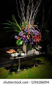Elaborate wedding buffet table with towering floral display with blue and red agapanthus.