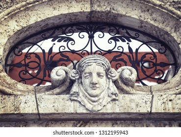 Elaborated window in an exterior wall with wrought iron ornaments and a caved marble woman head