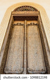 An elaborately carved exterior door with a glass arch and a carved gypsum surround in a restored traditional arabian house.
