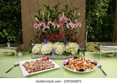 Elaborately decorated buffet table with vegetarian dishes and floral display.