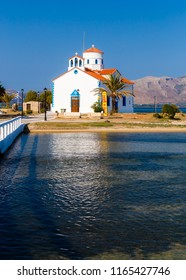 ELAFONISOS, LAKONIA - JULY 2018: Aghios Spyridon little white church with the sea surrounding it on the small island of Elafonosos, Lakonia, Greece