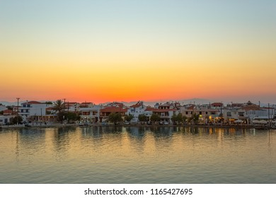 ELAFONISOS, LAKONIA - JULY 2018: Elafonisos city in distance in the afternoon with restaurants and sea reflections in Lakonia, Peloponnese, Greece
