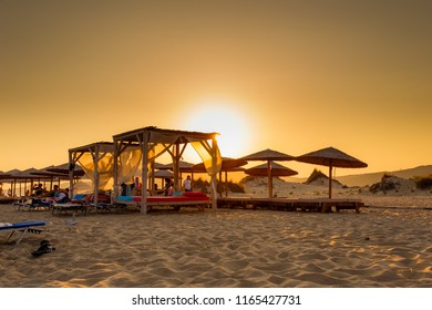 ELAFONISOS, LAKONIA - JULY 2018: Lines of sun beds at Simos beach in Elafonisos island in Greece against a hot summer sunset