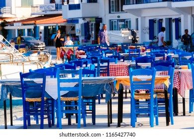 ELAFONISOS, LAKONIA - JULY 2018: Tables and chairs of restaurants  in front of the sea with out of focus background Elafonisos island, Lakonia, Greece