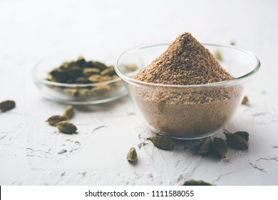 elaichi or Cardamom powder in bowl or heap over moody background with pods. selective focus