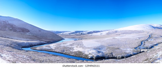 Elan Valley in Wales showing Afon Elan river flowing through a snowy panorama of a winter scene of mountains and blue sky.