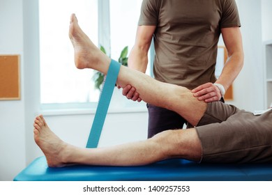 Elastic band exercises. Close up of a male leg being raised while doing a physical exercise with an elastic band