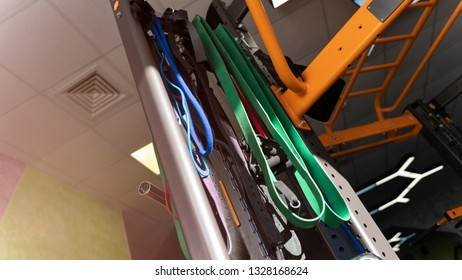 Elastic expanders of different colors hanging on a rack in sport gym. Sunlight falling on elastic tows hanging on a metal rack in sport gym. No people, new elastic equipment in gym