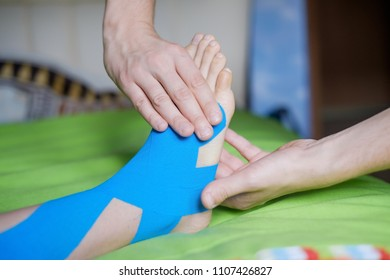 Elastic therapeutic blue tape applied to patient's left leg. Kinesio Taping therapy for injury