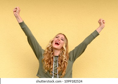 Elated joyful young woman cheering raising her fists in the air as she celebrates a success or good news over a yellow studio background