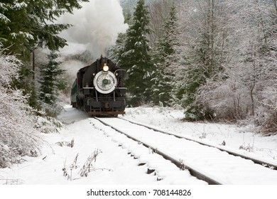 Elbe, WA, USA Dec. 3, 2005: Restored steam locomotive pulls restored passenger cars on scenic ride through snow covered forest near Elbe, Washington at base of Mt. Rainier
