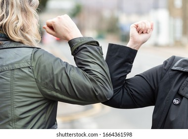 Elbow bump. New novel greeting to avoid the spread of coronavirus. Two women friends meet in a British street with bare hands. Instead of greeting with a hug or handshake, they bump elbows instead.