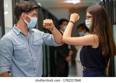 Elbow bump. New novel greeting to avoid the spread of coronavirus. Man and woma friends meet in workplacea Iinstead of greeting with a hug or handshake, they bump elbows instead.