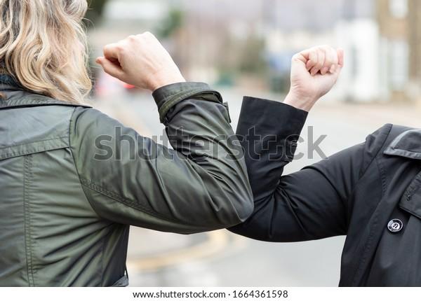 Golpe de codo. Nuevo saludo novedoso para evitar la propagación del coronavirus. Dos amigas se encuentran en una calle británica con las manos desnudas. En lugar de saludar con un abrazo o apretón de manos, en su lugar se golpean los codos.
