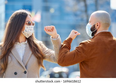 Elbow bumping. Elbow greeting to avoid the spread of coronavirus (COVID-19). Man and woman in the sunglasses meet with bare hands. Instead of greeting with a hug or handshake, they bump elbows.
