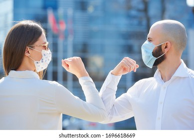 Elbow bumping. Elbow greeting to avoid the spread of coronavirus (COVID-19). Colleagues in shirts meet in the street with bare hands. Instead of greeting with a handshake or a hug, they bump elbows.