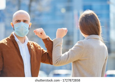 Elbow bumping. Elbow greeting to avoid the spread of coronavirus (COVID-19). Man with a beard and woman meet in the street. Instead of greeting with a hug or handshake, they bump elbows.