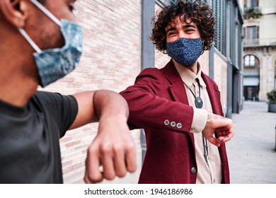 Elbow bumping. Elbow greeting to avoid the spread of coronavirus (COVID-19). Men in shirts meet in the street with bare hands. Instead of greeting with a handshake or a hug, they bump elbows