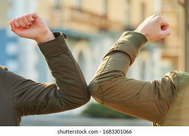Elbow greeting to avoid the spread of coronavirus (COVID-19). Man and woman meet in the street with bare hands. Instead of greeting with a hug or handshake, they bump elbows instead. A close-up photo.