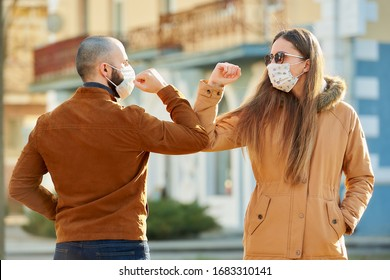 Elbow greeting to avoid the spread of coronavirus (COVID-19). A man and a woman in medical face masks meet on the street with bare hands. Instead of greeting with a hug or handshake, they bump elbows.