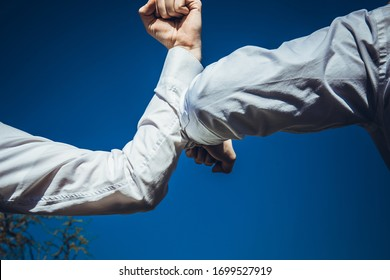 Elbow greeting to avoid the spread of coronavirus (COVID-19). Business mans meet in the office with bare hands. Instead of greeting with a hug or handshake, they bump elbows instead.
