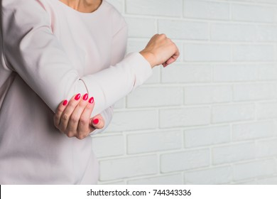 Elbow pain. Women holds her elbow with a hand. Injury, health problems, hand bending problem. Light background.