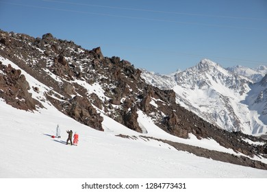 Elbrus Mountain / Russia - November, 2017: Snegurochka is striking a pose on a slope for photographer and Ded Moroz, who is slavic version of Santa Claus