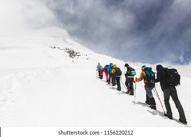 ELBRUS REGION, RUSSIA - JUNE 25, 2017: Group of tourists hiking to the top of mount Elbrus in Russia. Snowy and cold landscape around