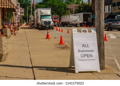 """ELBURN, IL/USA - JULY 24, 2018: A sign reminds passersby that local businesses will remain open during filming of scenes for the pilot of """"Lovecraft Country,"""" a 1950s-era TV drama to be aired on HBO."""