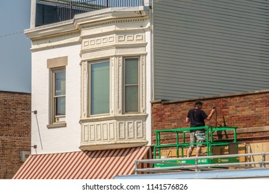 """ELBURN, IL/USA - JULY 24, 2018: A decorator touches up the brick facade of an old building that serves as a 1950s-era diner for """"Lovecraft Country,"""" a dramatic horror TV series to be aired on HBO."""