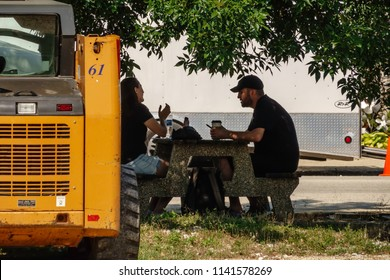 """ELBURN, IL/USA - JULY 24, 2018: Two production crew members take a break in streetside shade during preparations for filming of an upcoming TV pilot, """"Lovecraft Country,"""" for HBO."""
