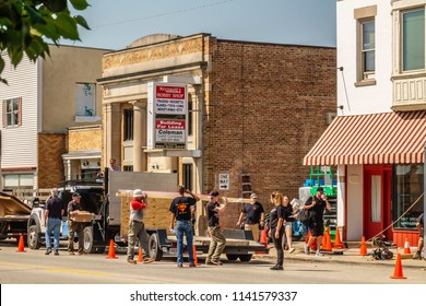 """ELBURN, IL/USA - JULY 24, 2018: A security guard watches a production crew help prepare a vintage set on Main Street for pilot scenes of """"Lovecraft Country,"""" a dramatic TV series to be aired on HBO."""