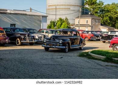 """ELBURN, IL/USA - JULY 25, 2018: A handler drives a vintage Plymouth from a parking lot with a collection of classic cars for scenes of """"Lovecraft Country,"""" a dramatic TV series to be aired on HBO."""